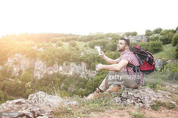 Angry hiker sitting on cliff peak and holding a map