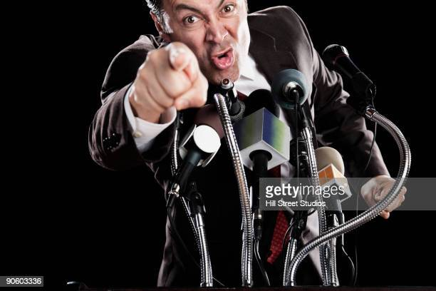 Angry Hispanic man pointing at podium with microphones