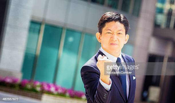 Angry Japanese businessman using fist to threaten