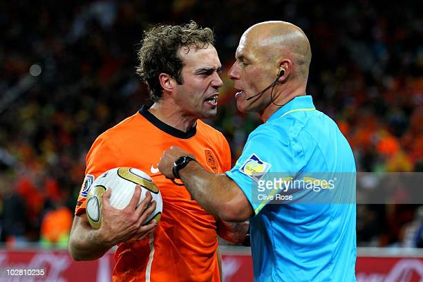 Angry Joris Mathijsen of the Netherlands argues with referee Howard Webb after he feels the goal scored by Andres Iniesta of Spain was offside during...