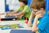 Angry kid looking at his craft at kindergarten