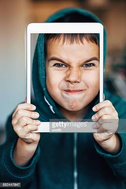 En colère petit garçon avec tablette numérique en selfie
