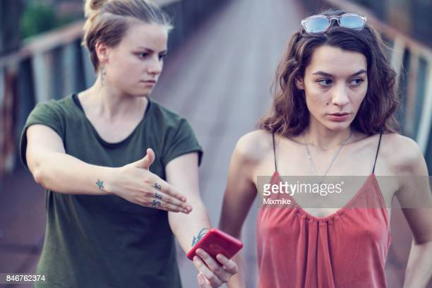Angry looking female pointing the mobile phone at another woman