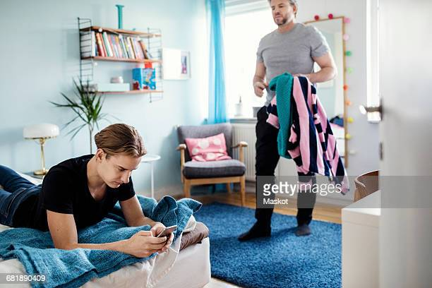 Angry man holding clothes while looking at son using smart phone on bed at new home