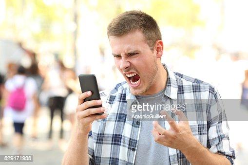 Angry man holding crashed phone : Stock Photo