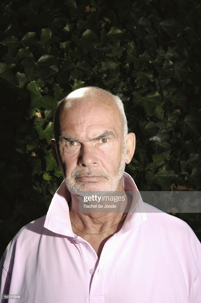 Angry man in pink t-shirt : Stock Photo