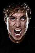 Man screaming angry aggressive at camera on black background. Young Caucasian mad male model. See more: