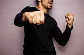 Angry multiracial man in black shirt is throwing punches