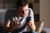 Single angry person with a mobile phone sitting on a sofa in the living room in a house indoor with a dark background