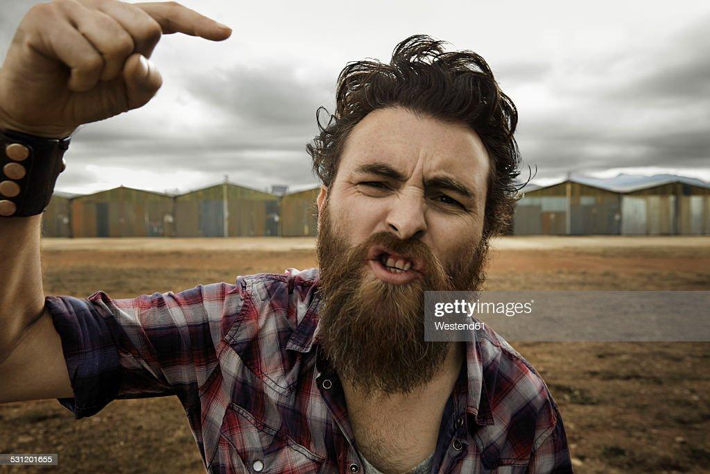 Angry man with full beard shouting at camera