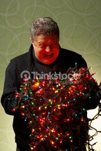 angry man with tangled christmas lights stock photo - Tangled Christmas Lights