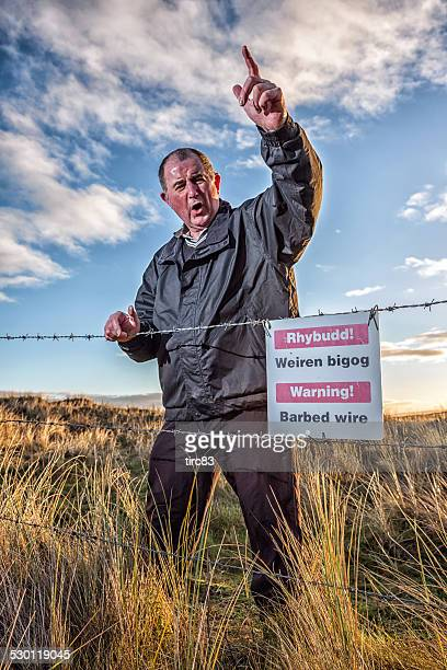 Angry mature red-faced farmer warning trespassers