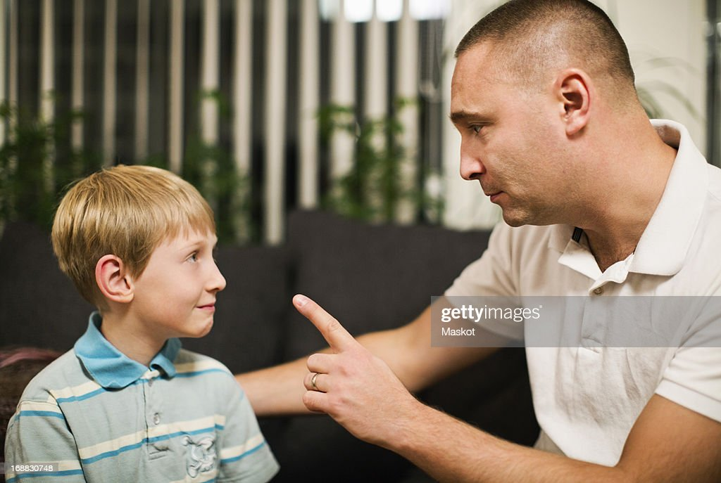 Angry mid adult man disciplining son at home : Stock Photo