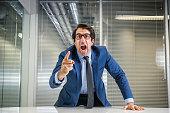 Nerdy caucasian mid thirties businessman in glasses yelling.