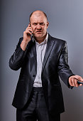 Angry not undestanding gloomy stressed angry business man talking on mobile phone very emotional in office suit on grey background. Closeup portrait