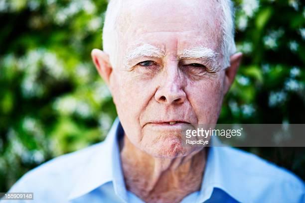 Angry old man glares at camera