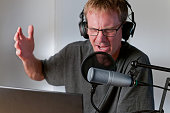 Horizontal image of a male radio host or podcaster sitting at his desk while he records his show in a small sound room. He is wearing headphones and has a studio microphone with a pop filter on a boom