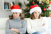 Angry roommates or sisters in christmas sitting on a couch in the living room at home