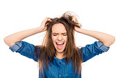 Angry sad young woman with damaged hair screaming