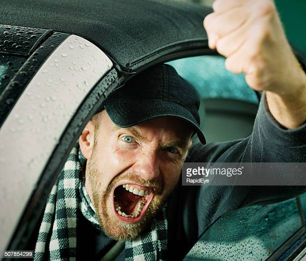 Angry, scary looking driver shakes fists threateningly through car window