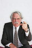Angry senior businessman pointing to camera