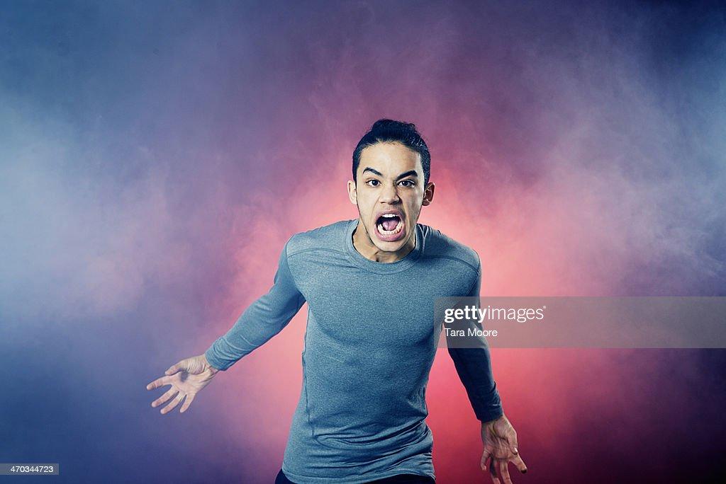 angry sports man running through smoke