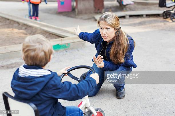 Angry teacher shouting at boy on tricycle