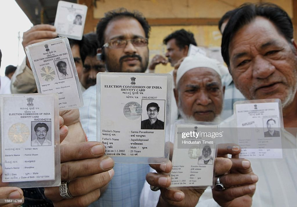Angry voters showing their voter cards as their names are missing from the voting list during the first phase of Gujrat state assembly elections on December 13, 2012 in Surat, India.