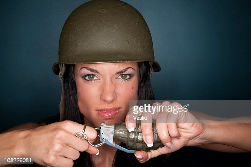 Angry woman holding a grenade and wearing an army helmet