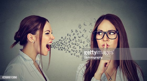 Angry woman screaming at herself with finger on lips gesture : Foto de stock