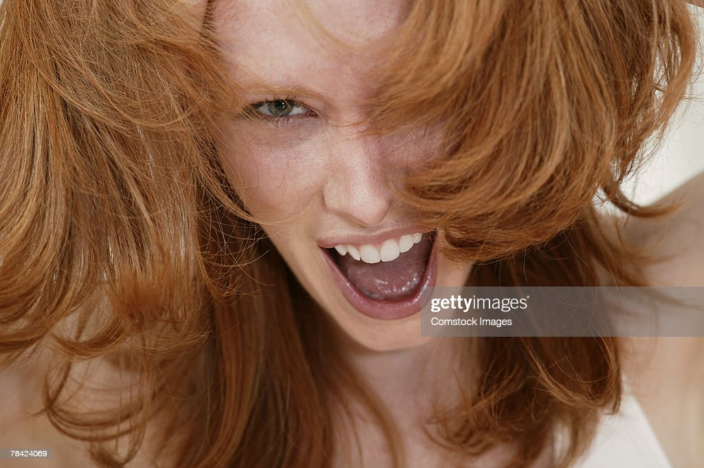 Angry woman screaming with hands in hair : Stock Photo