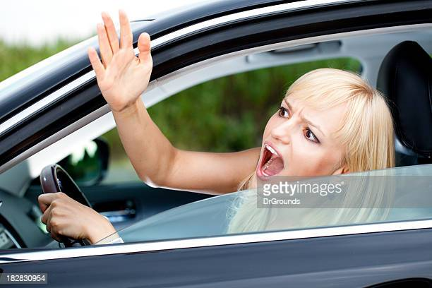 Angry woman with road rage driving a car