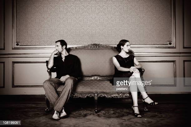 Angry Young Couple Sitting Far on Couch
