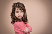 Angry and pouting cute young girl with crossed arms