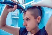 Angry young girl shave the hair on the blurred background