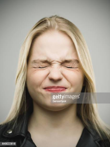 Angry young woman clenching eyes