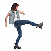 Young woman in jeans vest and black boots is shouting and kicking. Side view. Full length studio shot isolated on white.