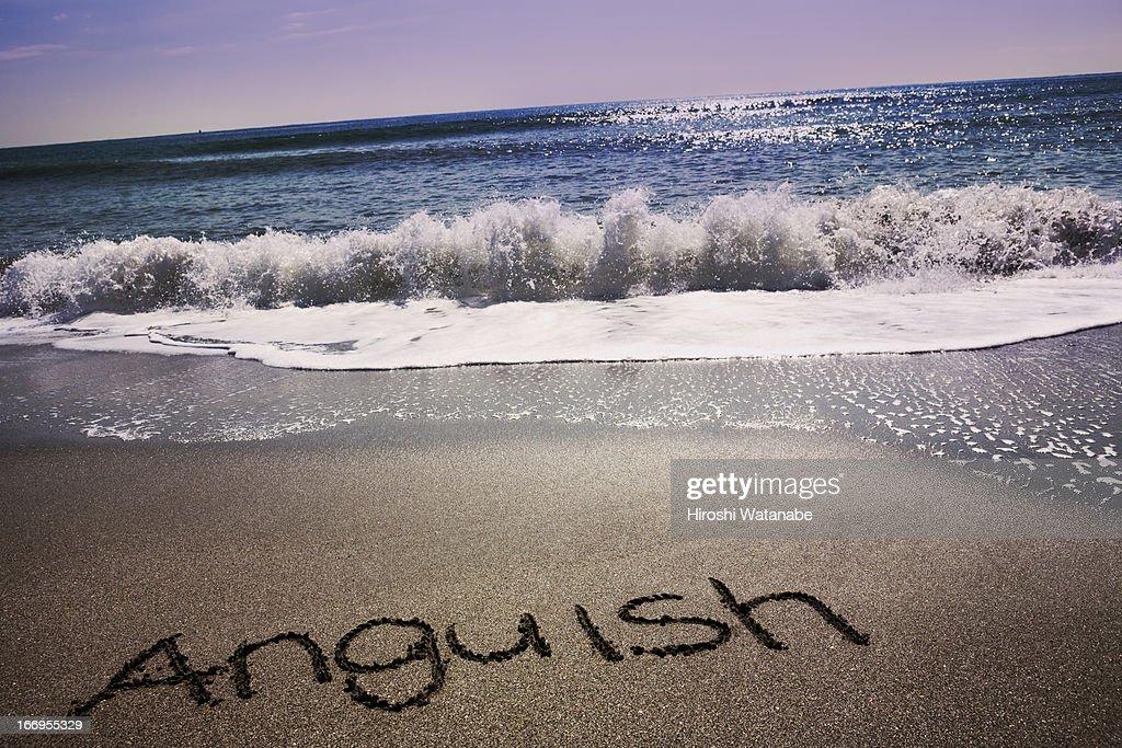 'Anguish' written in sand on beach : Stock Photo
