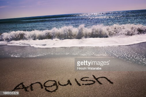 'Anguish' written in sand on beach : Stock Photo