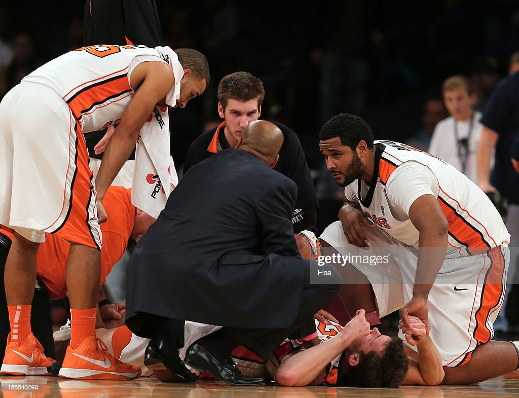 Angus Brandt of the Oregon State Beavers is tended to by head coach Craig Robinson and teammates Joe Burton and Roberto Nelson in the second half...