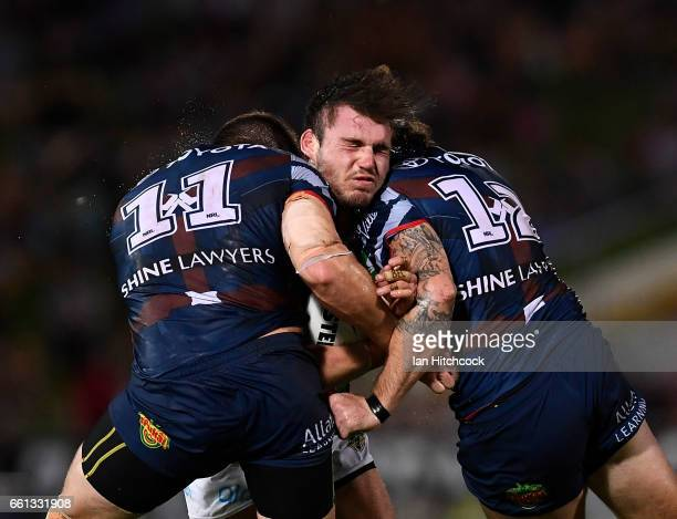 Angus Crichton of the Rabbitohs is tackled by Gavin Cooper and Ethan Lowe of the Cowboys during the round five NRL match between the North Queensland...
