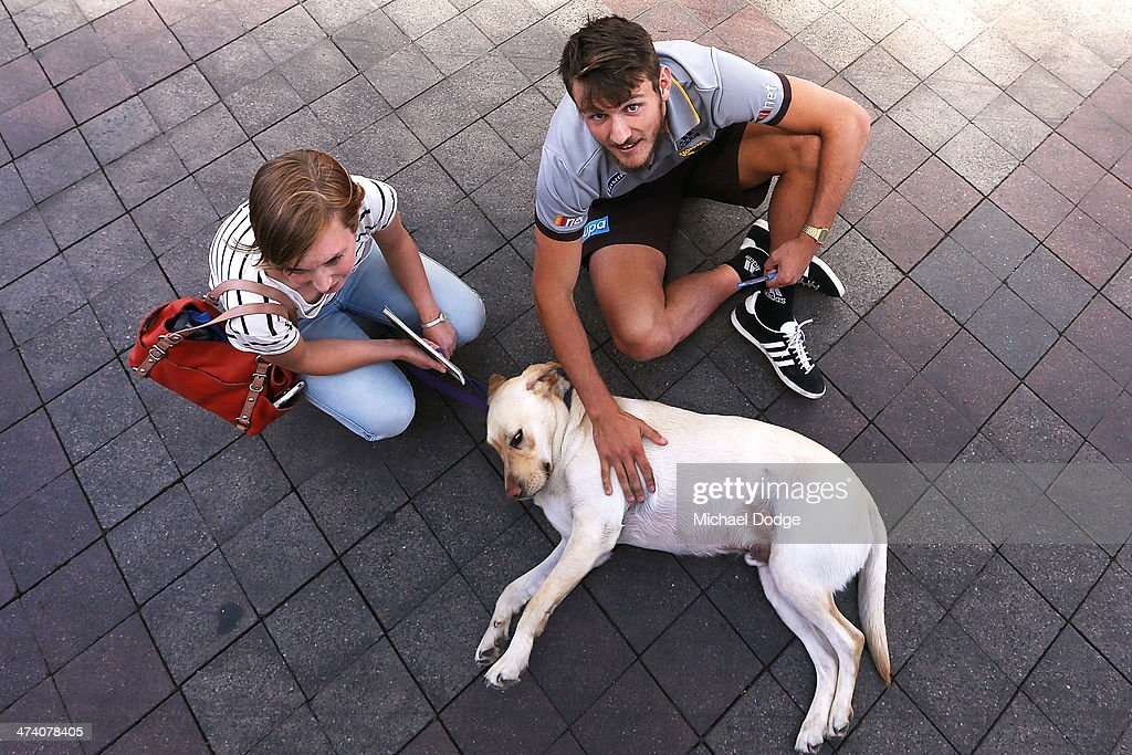 Angus Litherland pats a Guide dog for the Guide Dogs Tasmania 'Take the Lead' campaign launch during the Hawthorn Hawks AFL Community Camp on February 22, 2014 in Launceston, Australia.