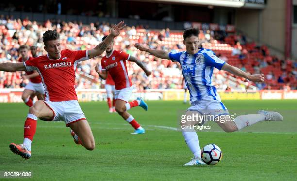 Angus MacDonald of Barnsley attempts to block a shot made by Joe Lolly of Huddersfield Town during the pre season friendly at Oakwell Stadium on July...