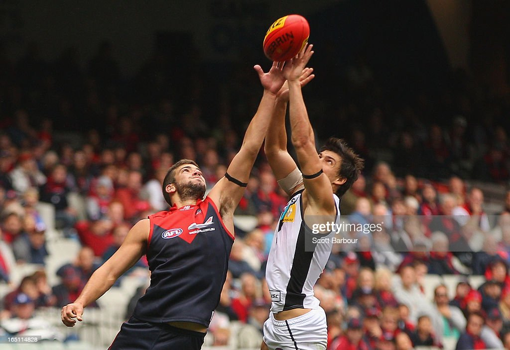 Angus Monfries of the Power and Jimmy Toumpas of the Demons compete for the ball during the round one AFL match between the Melbourne Demons and Port Adelaide Power at the Melbourne Cricket Ground on March 31, 2013 in Melbourne, Australia.
