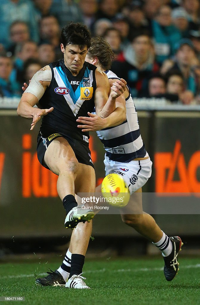 <a gi-track='captionPersonalityLinkClicked' href=/galleries/search?phrase=Angus+Monfries&family=editorial&specificpeople=221019 ng-click='$event.stopPropagation()'>Angus Monfries</a> of the Power kicks whilst being tackled by Mitch Duncan of the Cats during the Second Semi Final match between the Geelong Cats and the Port Adelaide Power at Melbourne Cricket Ground on September 13, 2013 in Melbourne, Australia.