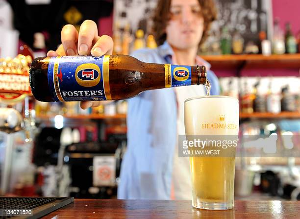 Angus Page pours a glass of Foster's beer at the Drop Bear Inn in South Melbourne on November 25 2011 Australia's government approved brewer...