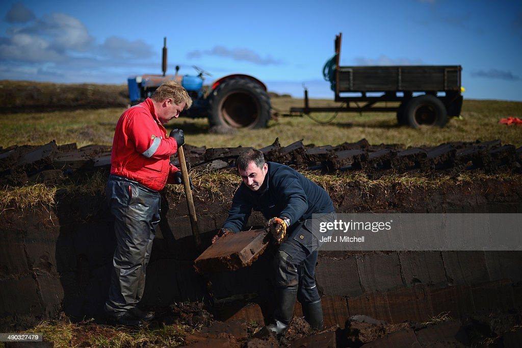 Angus Smith, and Callum Mckenzie extract peat from a moor near the village of Cross on May 13, 2014 in Lewis, Scotland. The tradition of peat cutting has seen a revival over recent years in the Outer Hebrides as residents conscious of rising fuel cost are using it to run their central heating and stove fires. A referendum on whether Scotland should be an independent country will take place on September 18, 2014.