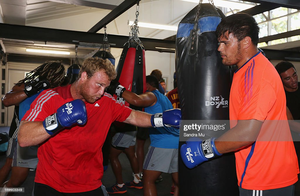 Angus Ta'avao (R) holds the bag for Luke Braid during a Blues training session with Shane Cameron at Shane Cameron Fitness on January 23, 2013 in Auckland, New Zealand.