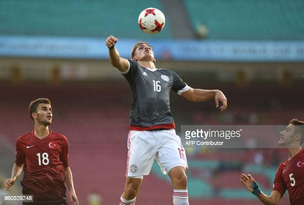 Anibal Vega of Paraguay Abdussamed Karnucu and Ozan Kabak of Turkey vie for the ball during the group stage football match between Turkey and...