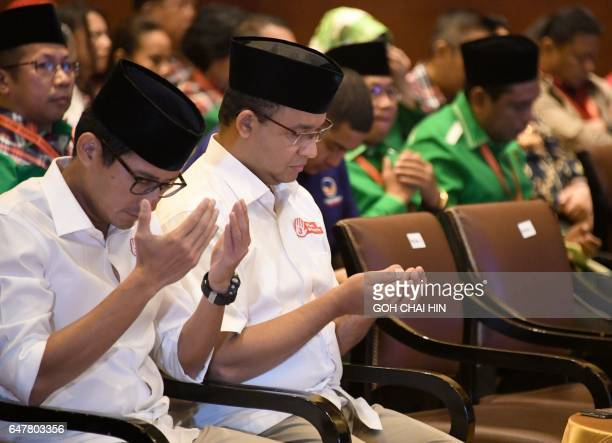 Anies Rasyid Baswedan and his running mate Sandiaga Salahuddin Uno pray during an event held by the election commission to introduce the candidates...